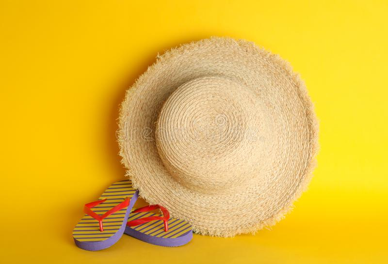 Straw hat and flip flops on color background, space for text royalty free stock images