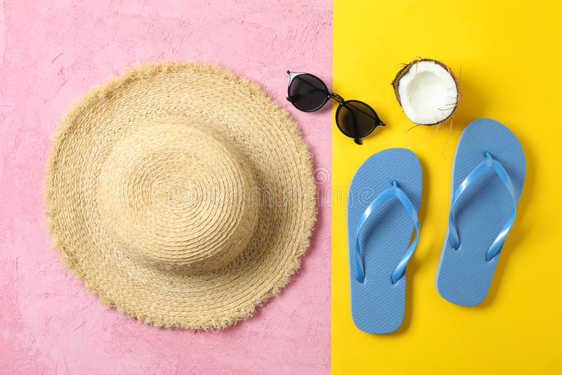 Straw hat, flip flops, sunglasses and coconut on two tone background, space for text and top view. Summer vacation. Backdrop royalty free stock photos