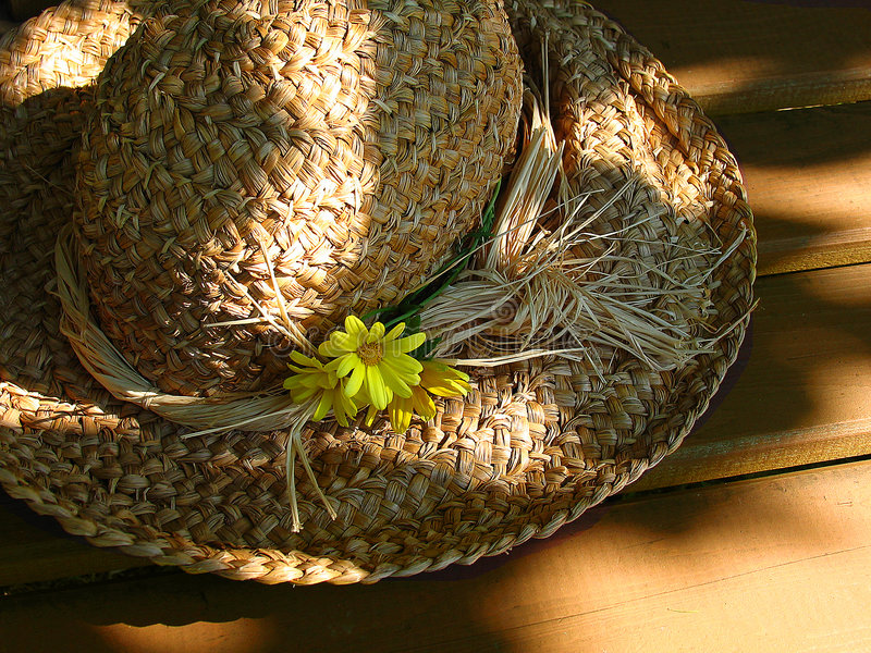 Straw hat with flowers. Straw hat on cedar bench royalty free stock photos