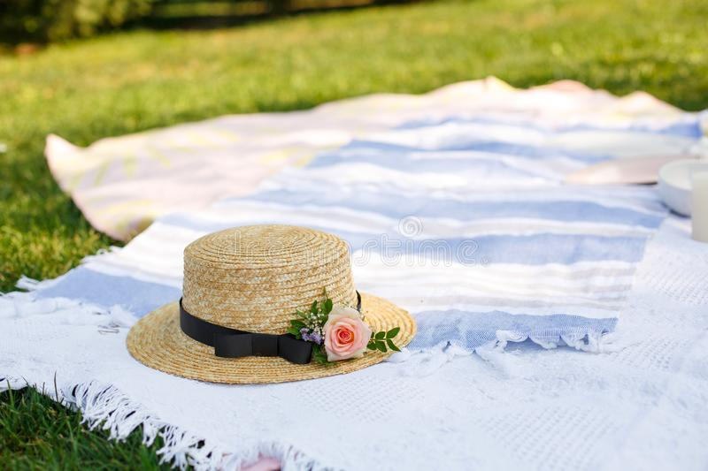 Straw hat with fresh flowers lay on a white picnic blanket at green lawn bright summer day background. Summer weekends leisure stock images