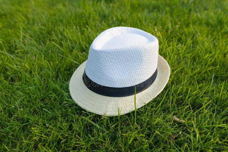 Straw hat on green grass lawn texture.  stock photos