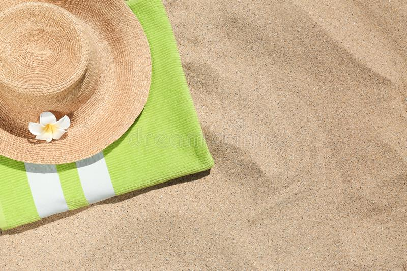 Straw hat with green towel and space for text on golden sand. Beach objects royalty free stock images