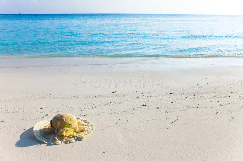 Straw hat lay on sand at edge of sea