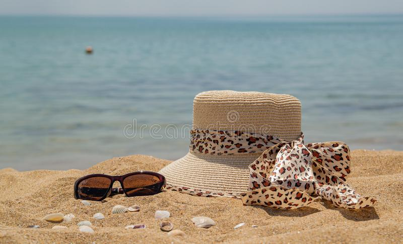 A straw hat for a leopard-print woman, sunglasses and seashells by the sea. stock photos