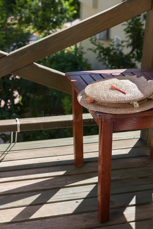Straw hat lies on simple wooden stool. The stool stands on small open balcony. Sunny day, summer. Contrast lighting, light and shadow royalty free stock image