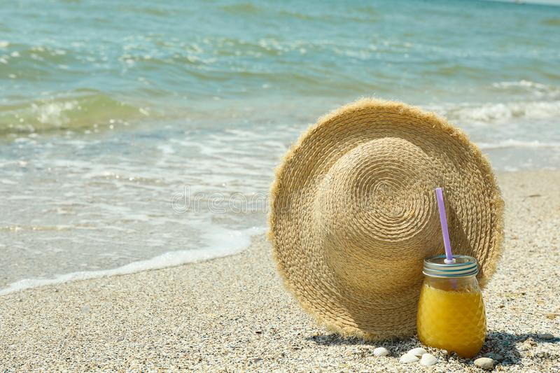 Straw hat and orange juice on seaside, space for text. Summer vacation stock photo