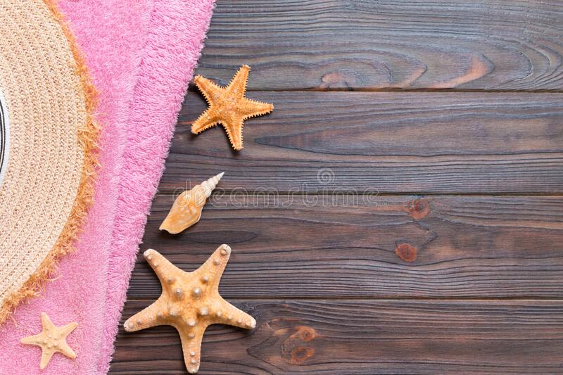 Straw hat, pink towel and starfish On a dark wooden background. top view summer holiday concept with copy space.  stock image