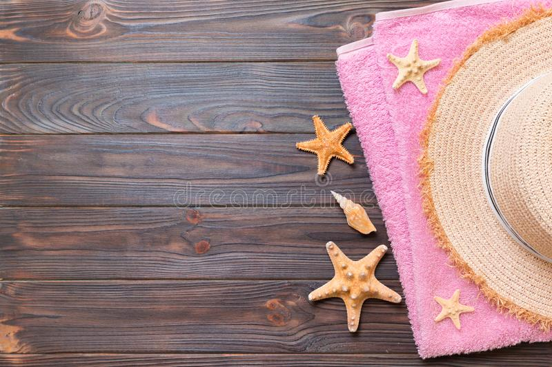 Straw hat, pink towel and starfish On a dark wooden background. top view summer holiday concept with copy space stock image