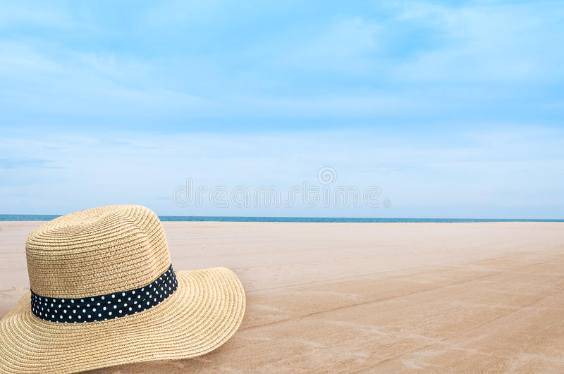 Straw hat on the shore of a beach,Woven fedora hat on sand background stock photo