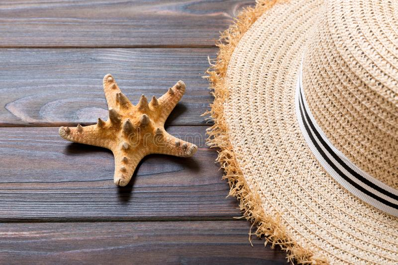 Straw hat and starfish On a dark wooden background. top view summer holiday concept with copy space stock photo