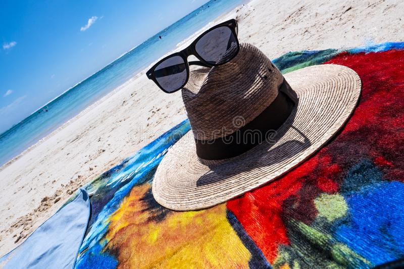 Straw hat, sun glasses and flip flops on a tropical beach royalty free stock photos