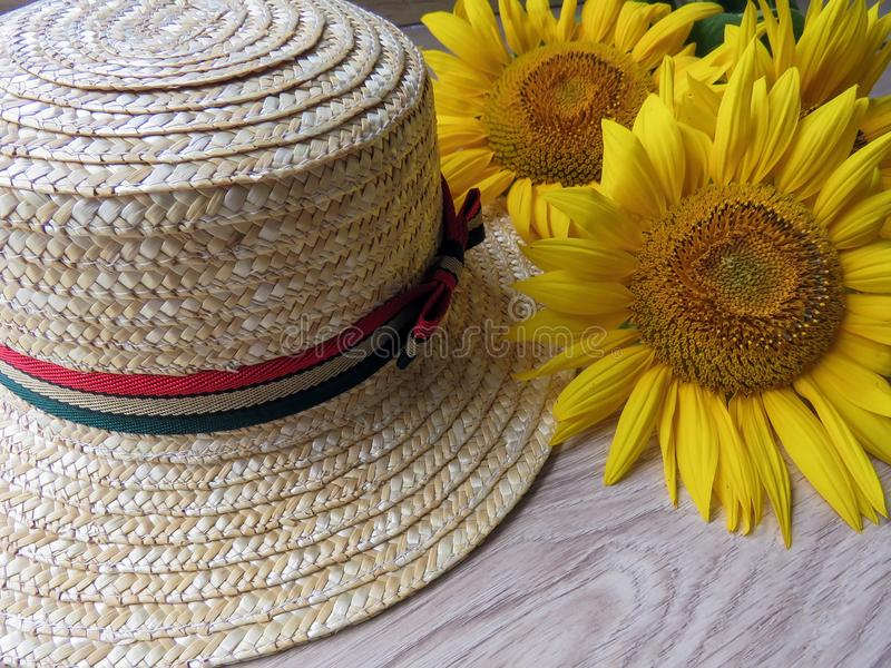 Straw Hat and sunflowers on wooden background stock photo