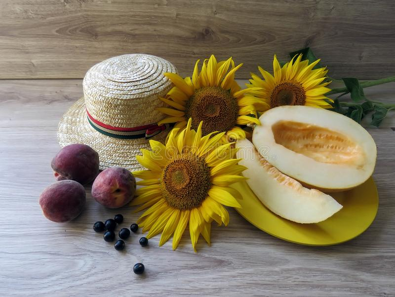 Straw Hat and sunflowers on wooden background royalty free stock photography