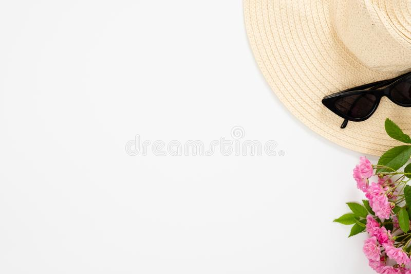 Straw hat, sunglasses, bouquet of pink rose flowers on white background. Top view, minimal flat lay style composition . Fashion. Blog banner mockup with copy royalty free stock photo