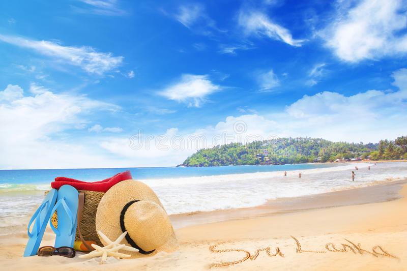 Straw hat, sunglasses, slippers and a bag on the golden sand of Sri Lanka`s beach royalty free stock image