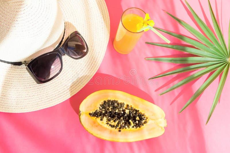 Straw Hat Sunglasses Tall Glass con frutta tropicale Juice Papaya Palm Leaf su fondo fucsia Perdite di luce solare Vacanza di est immagine stock