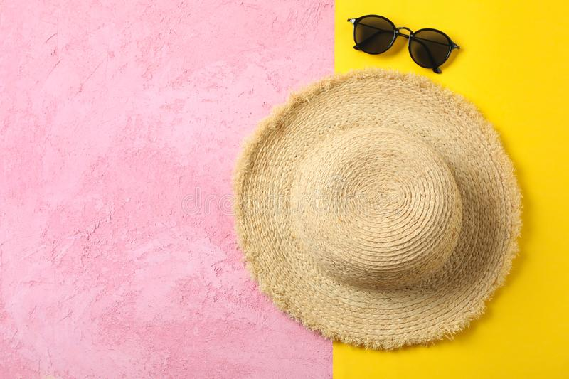 Straw hat and sunglasses on two tone background, space for text and top view. Summer vacation. Backdrop royalty free stock images