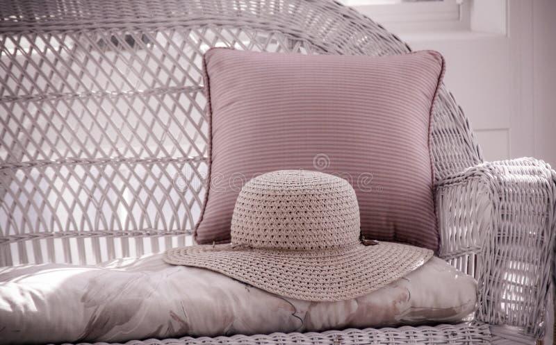 Straw Hat sur Loveseat en osier photographie stock