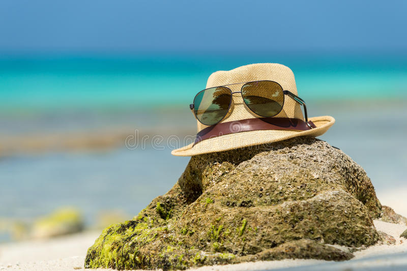 Straw hat, towel beach sun glasses and flip flops on tropical royalty free stock photography
