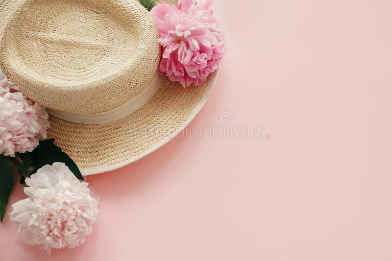 Straw hat with white and pink peonies on pastel pink paper. Hello spring image with copy space. Summer vacation concept. International Women`s Day. Happy royalty free stock image