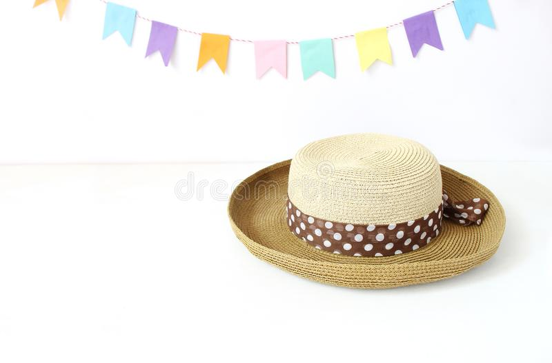 Straw hat on white table with colorful party flags, bunting decoration. Greeting card, invitation for summer birthday or royalty free stock photo