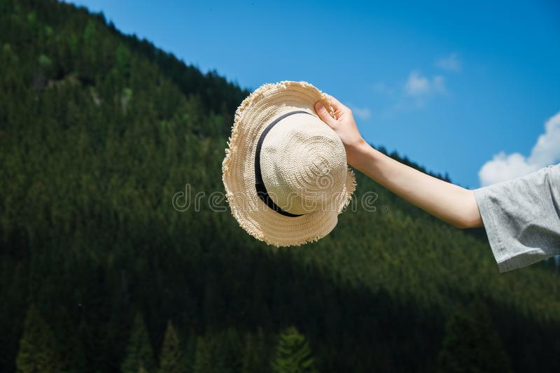 Straw hat in woman`s hand, mountain landscape royalty free stock photos