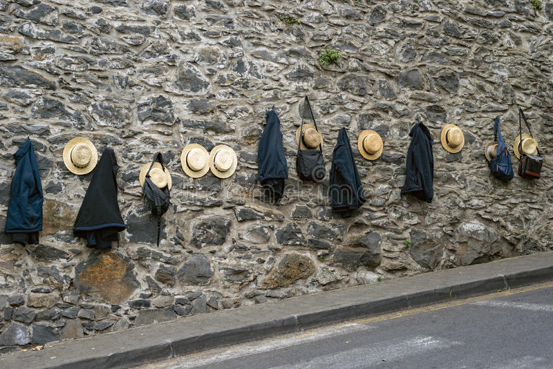 Straw hats and jackets of traditional basket sledge riders, Funchal, Madeira Island. Typical straw hats and jackets of sledge riders on stone wall while riders royalty free stock photo