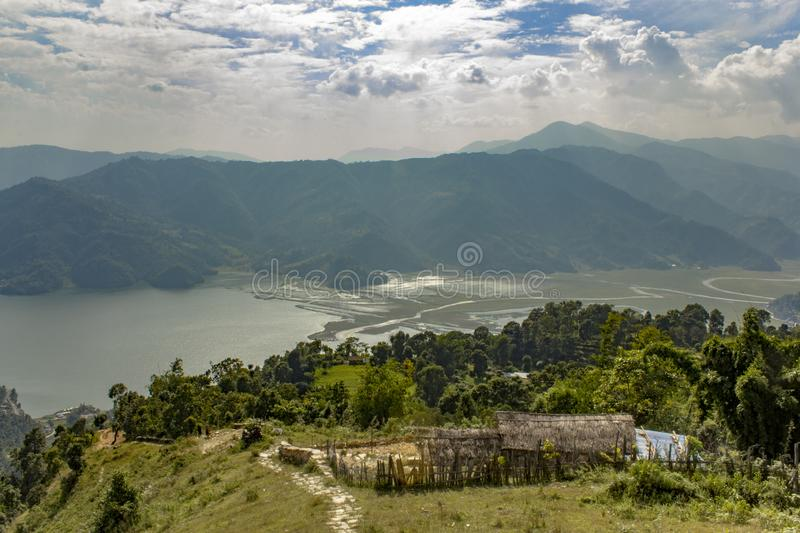 Straw hut on a hillside against the backdrop of a green mountain valley with a lake stock images