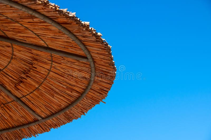 Straw roof of sun umbrella against the blue sky. Vacation topic.summer beach, background for an inscription.Texture of stock photo