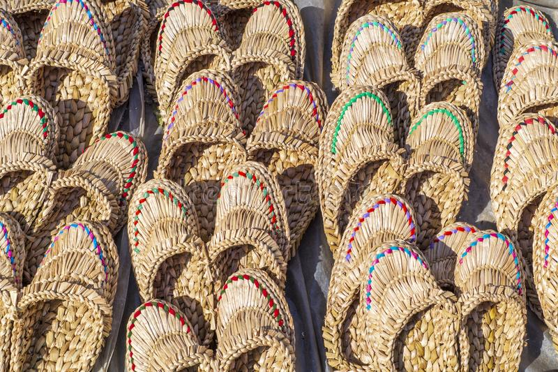 Straw Slippers som ?r till salu, f?r kvinnor eller m?n av ljusa f?rger royaltyfria foton