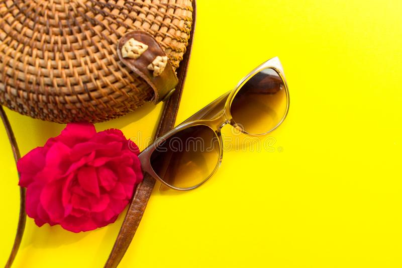 Straw stylish  women`s summer bag and sunglasses and a red rose flower on a yellow background. Summer vacation concept stock images