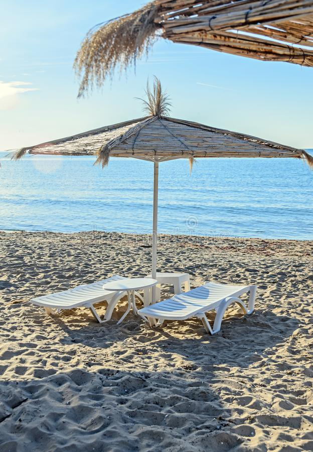 Straw sun umbrellas and white plastic sunbeds, beach with sand stock photography