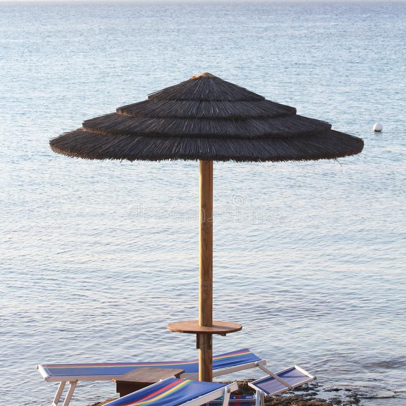 Straw umbrella against blue sea and sky. Two deckchairs remain under the umbrella.  stock photo