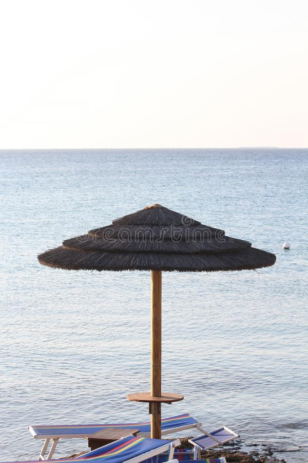 Straw umbrella against blue sea and sky. Two deckchairs remain under the umbrella.  royalty free stock image