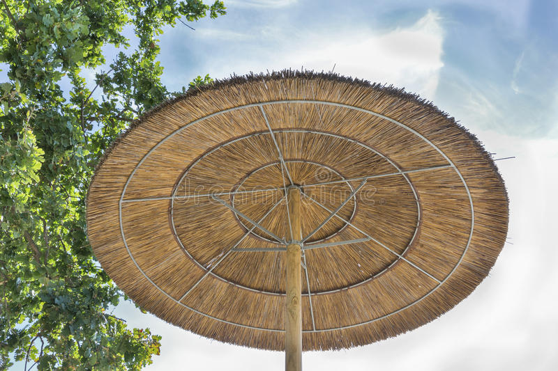 Straw umbrella on a background of blue sky. bottom view royalty free stock images