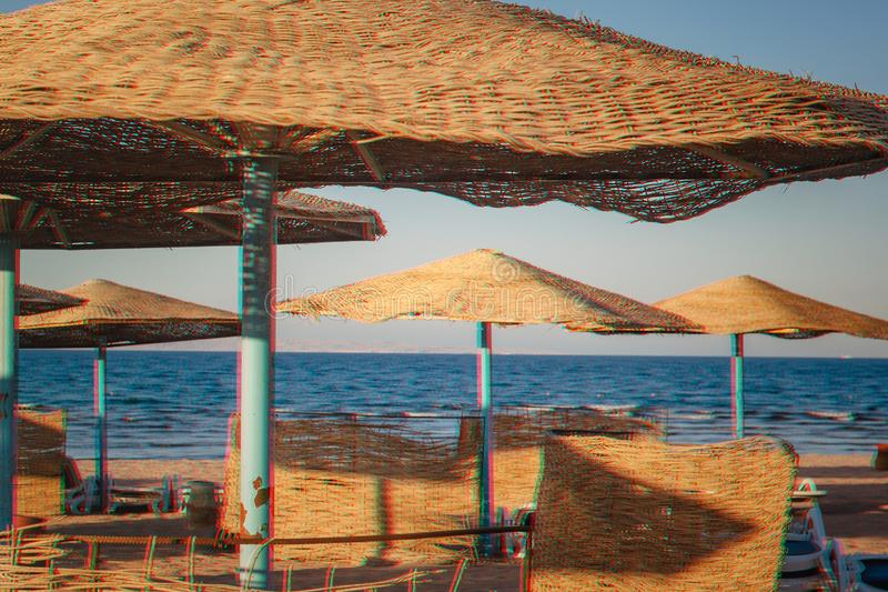 Straw umbrellas on the beach. glitch Anaglyph 3d effect. twisted shabby coral turquoise effect.  royalty free stock photos
