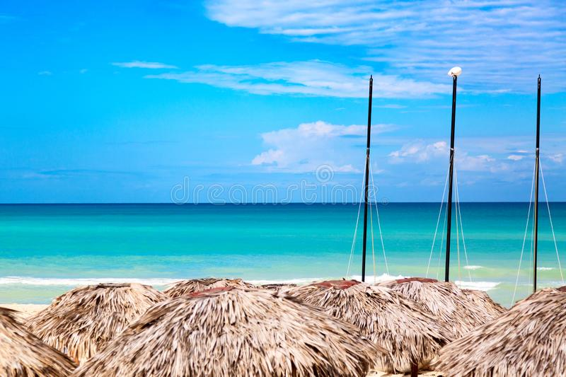 Straw umbrellas with sailboats on the beach in Varadero, Cuba. Vacation concept stock image