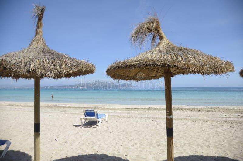 Straw Umbrellas su Sandy Beach fotografia stock libera da diritti