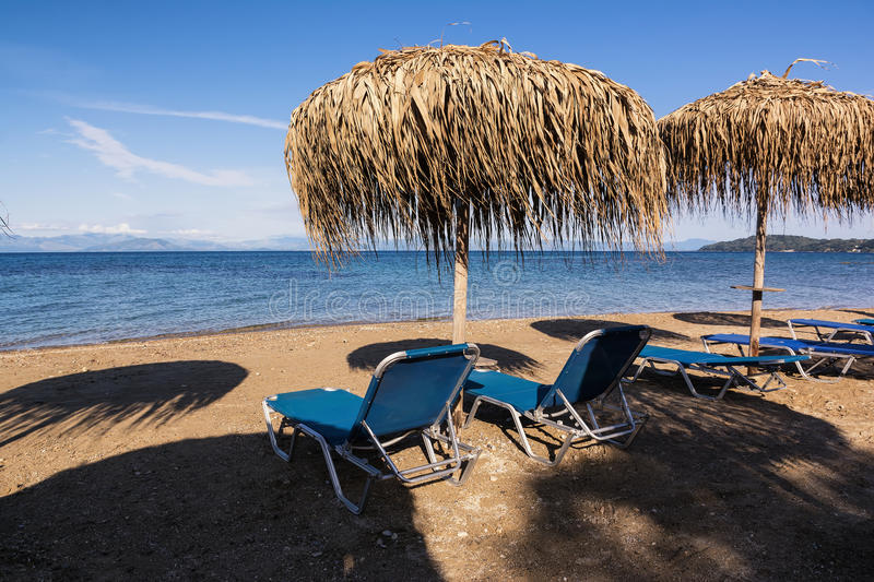 Straw umbrellas and sunbeds on a sandy beach, Corfu, Greece stock image
