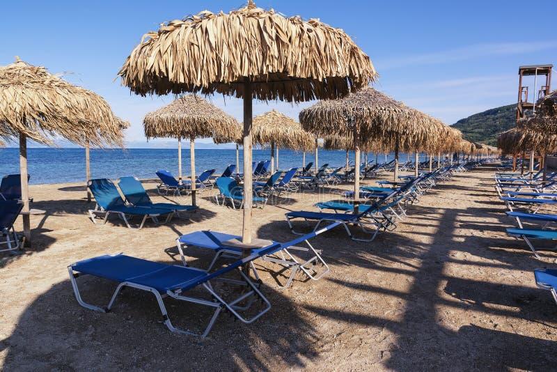 Straw umbrellas and sunbeds on a sandy beach, Corfu, Greece stock image
