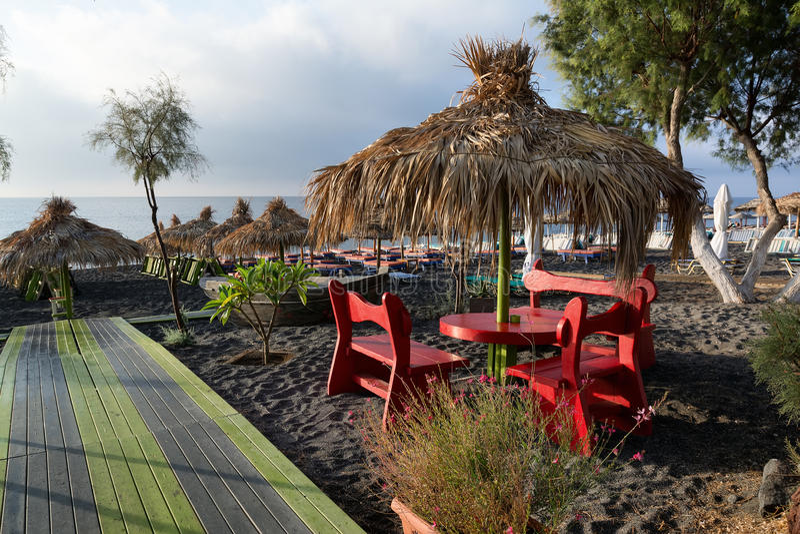 Straw umbrellas and tanning beds on Perissa beach, Santorini, Greece royalty free stock photography