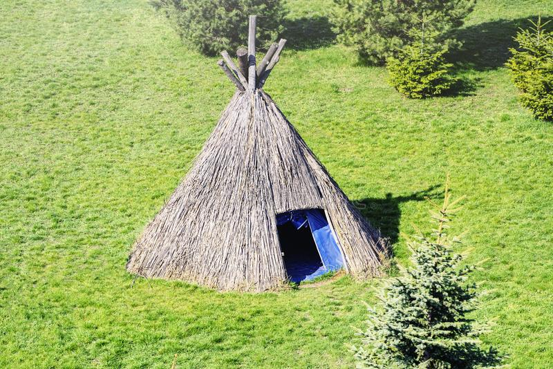 Straw wigwam on a glade on a sunny spring day. Wigwam type thatch huts. Wigwam type thatch huts .Straw wigwam on a glade on a sunny spring day stock photography
