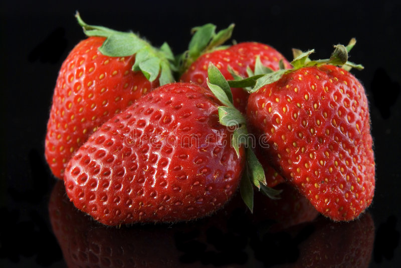 Strawberries. Flashing red strawberries on a black background stock photos