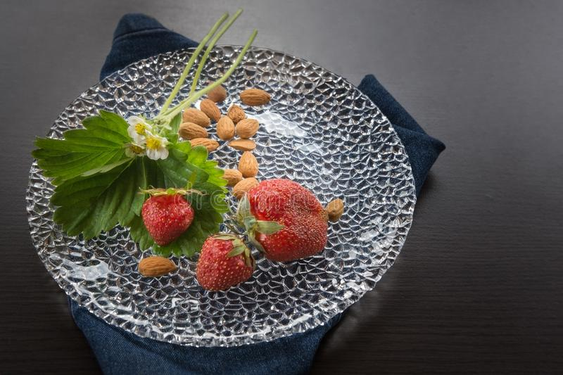 Strawberries and almonds, healthy snack on glass plate royalty free stock photo