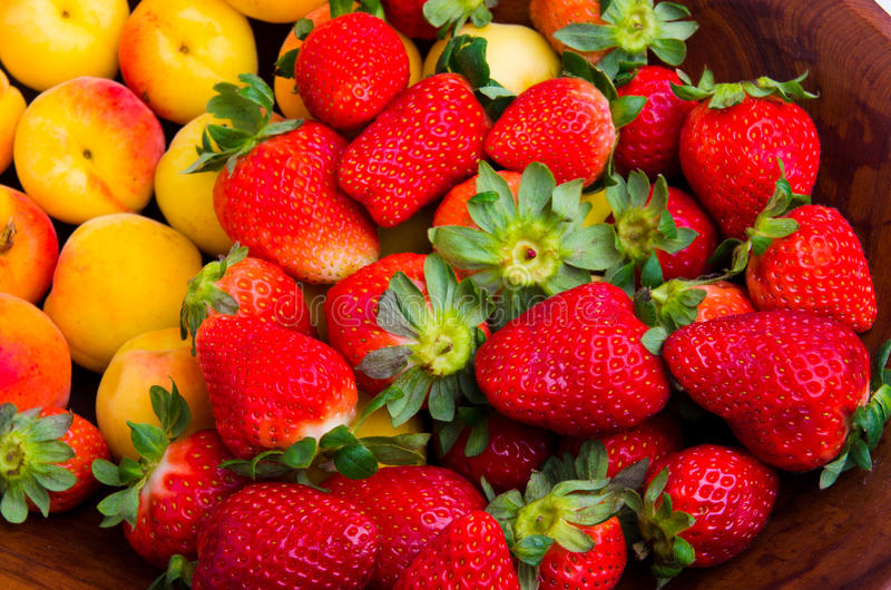 Strawberries and apricots. Delicious pile of strawberries and apricots over wood royalty free stock photography