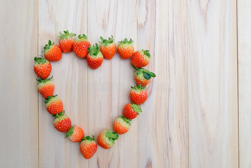 Strawberries array heart shape on wooden table with copy space stock images