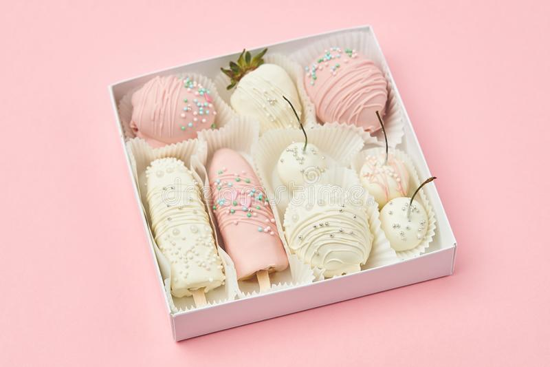 Strawberries, bananas, cherries and apricots coated with white and pink chocolate are lie in a gift box stock image