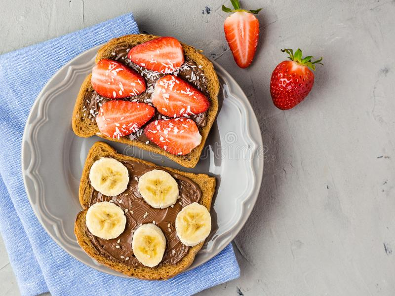 Toast with chocolate and fruits on a gray plate. Strawberries and bananas on stone kitchen table background. Top view stock photos