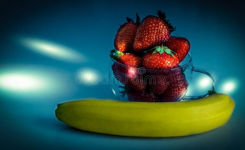 Strawberries and bananas are on the table. Dessert royalty free stock image