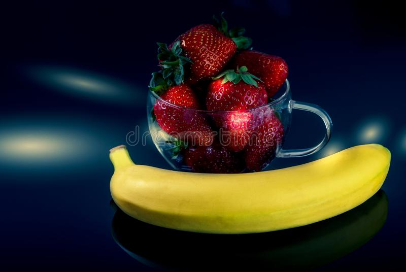 Strawberries and bananas are on the table. Dessert stock photos